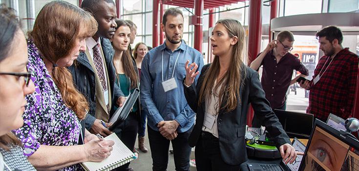 Une étudiante qui présente à des juges lors d'une compétition de désign.