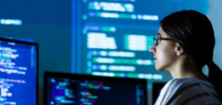 Une fille portant des lunettes devant plusieurs ordinateurs