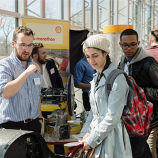 students examining car