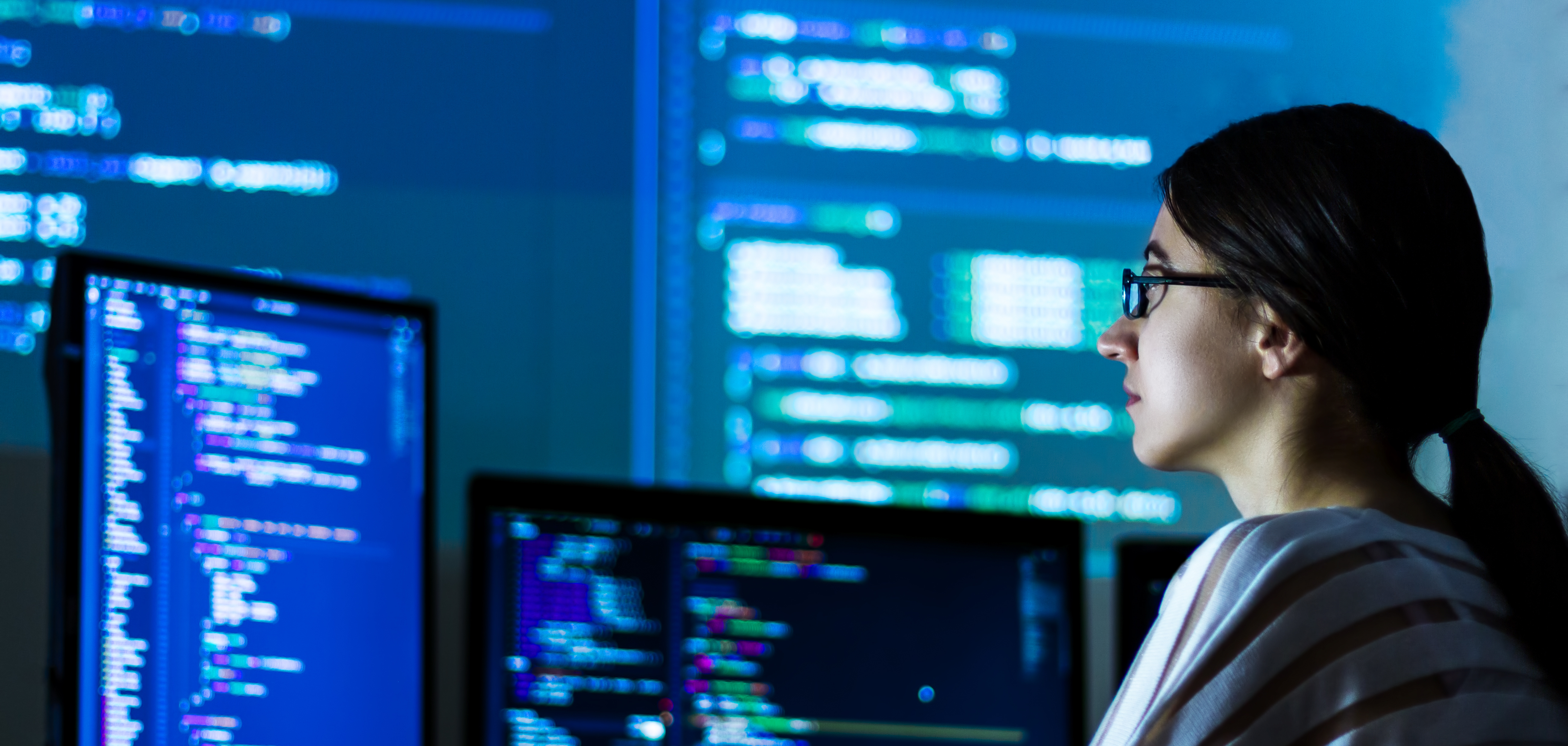 A girl with glasses in front of many computer screens.