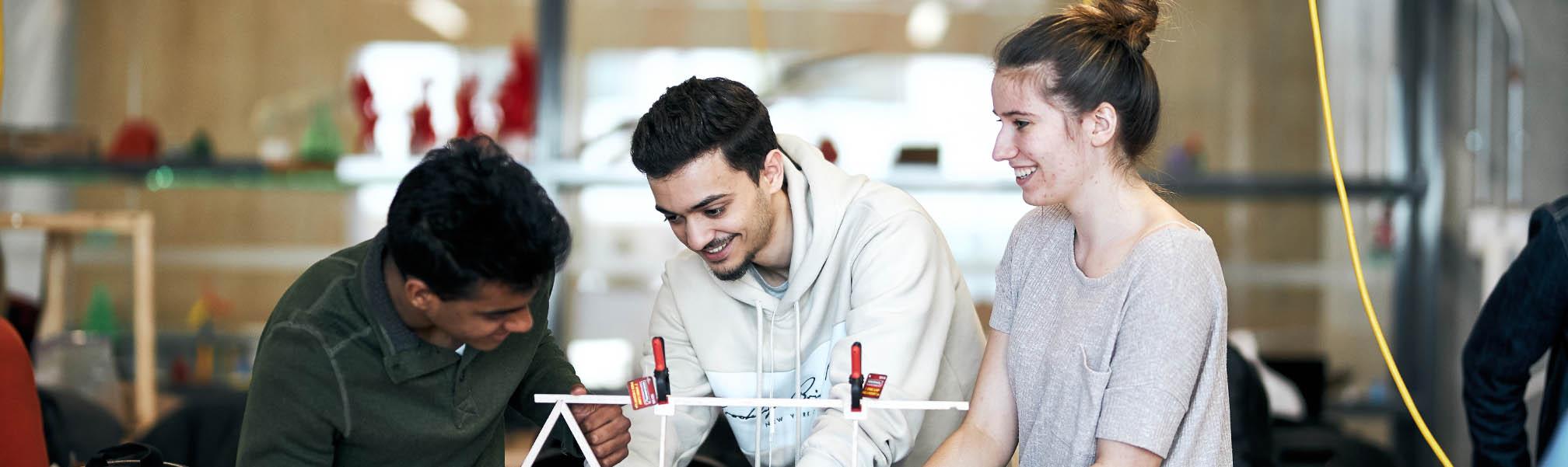 Trois étudiants souriant en travaillant sur une maquette