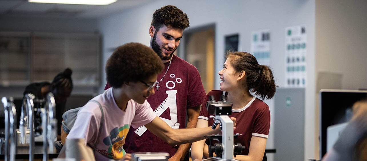 Un groupe d'adolescent discutant autour d'un microscope