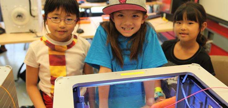 Des ados jettent un coup d'oeil dans une imprimante 3D.