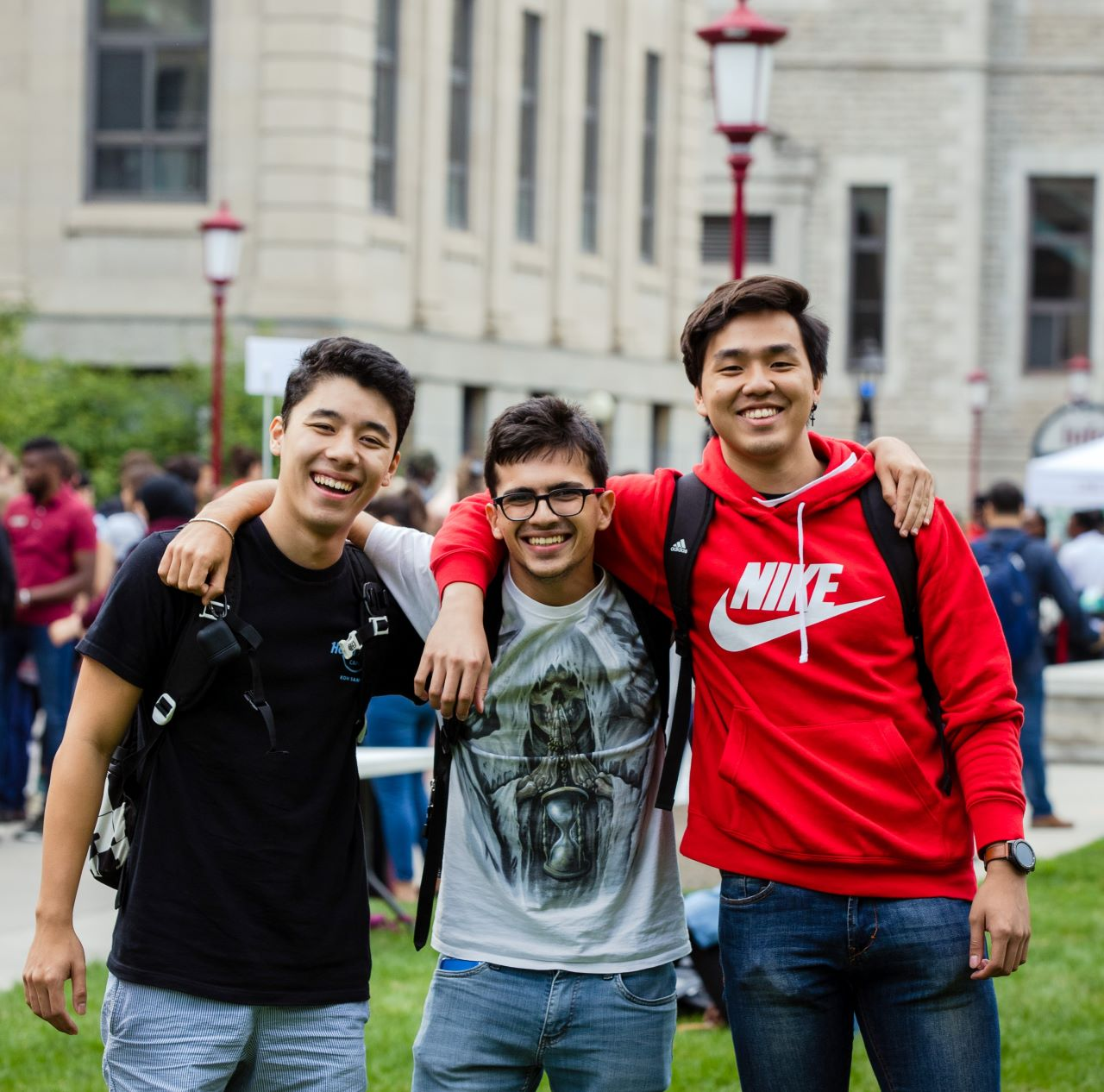 Group of three friends with their arms around each other's neck