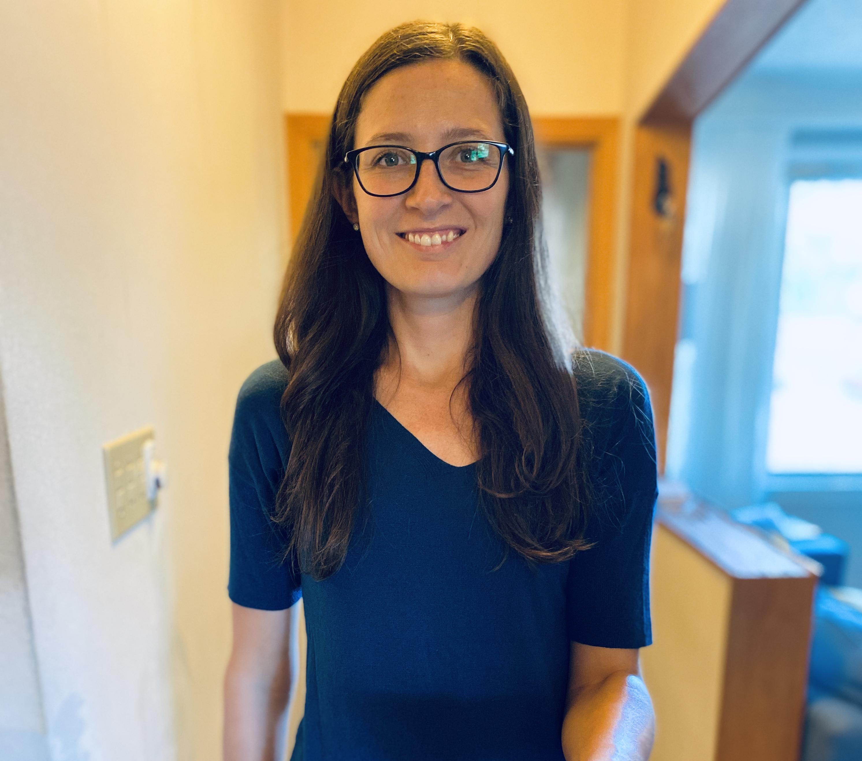 Femme avec cheveux bruns, lunettes et gilet bleu dans une maison
